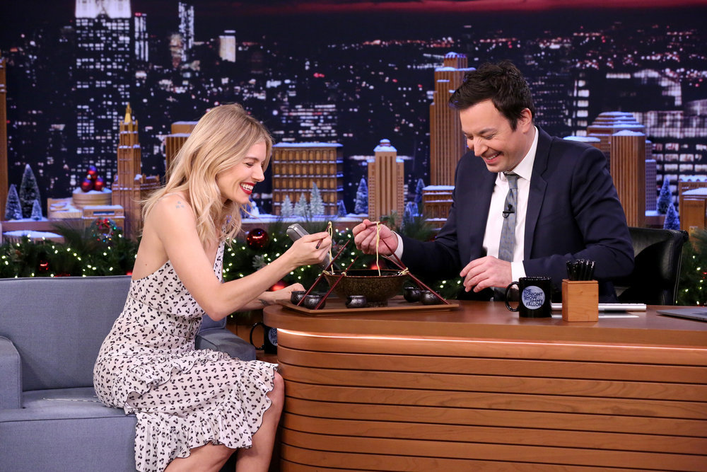 "THE TONIGHT SHOW STARRING JIMMY FALLON -- Episode 0592 -- Pictured: (l-r) Actress Sienna Miller and host Jimmy Fallon take part in ""The Ramen Challenge"" on December 15, 2016 -- (Photo by: Andrew Lipovsky/NBC)"
