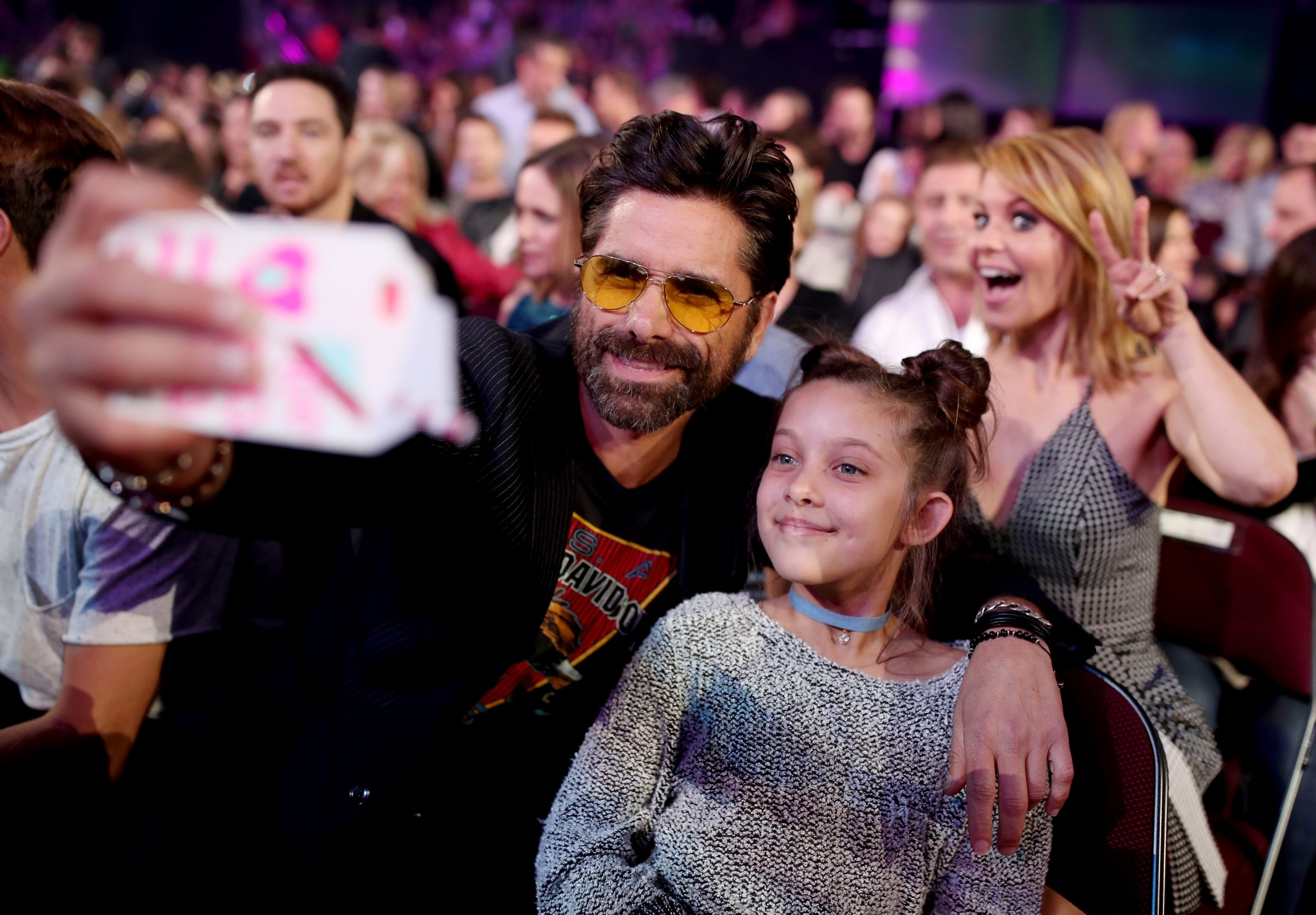 LOS ANGELES, CA - MARCH 11:  Actor John Stamos (L) takes a selfie with a fan while actor Candace Cameron Bure (R) photobombs at Nickelodeon's 2017 Kids' Choice Awards at USC Galen Center on March 11, 2017 in Los Angeles, California.  (Photo by Chris Polk/KCA2017/Getty Images for Nickelodeon)